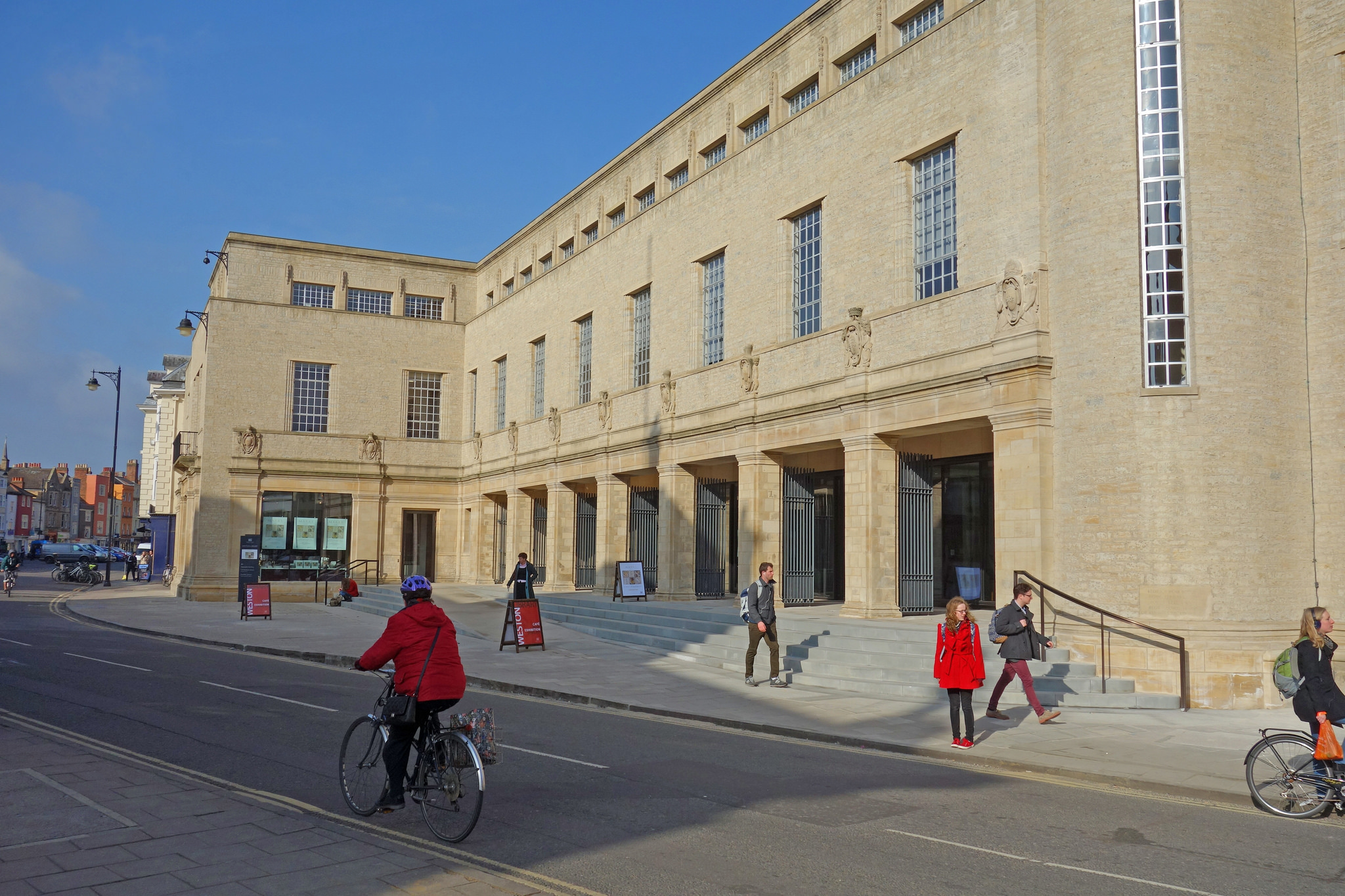 A view of the Weston Library, a large stone building, with some people walking in front of it