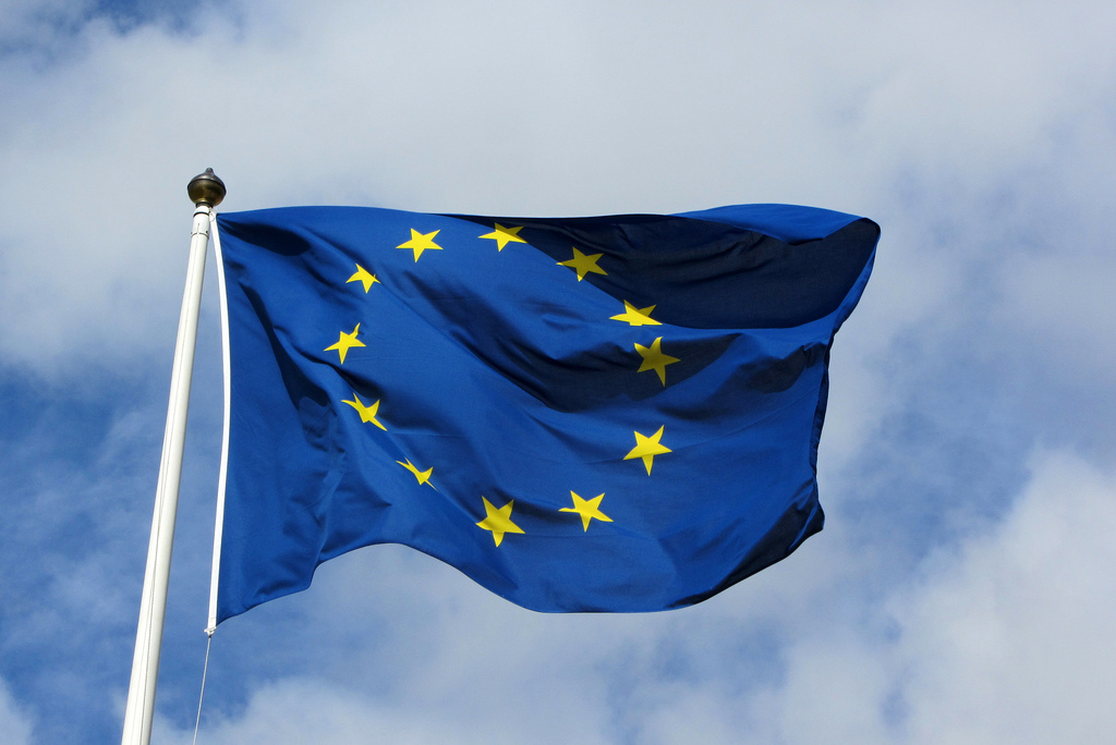 The flag of the European Union blowing in the wind with the sky in the background