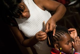 A mother braids her daughter's natural hair.