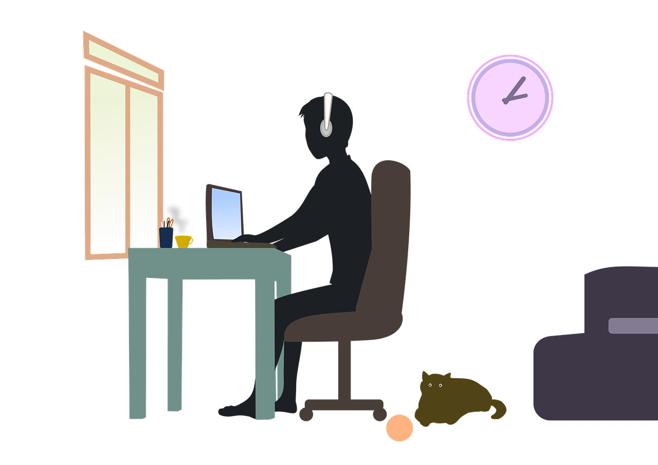 Figure with headphones working at desk with laptop
