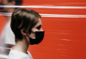 Two figures walking in opposite directions with face masks
