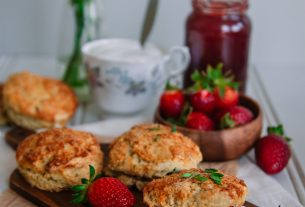 Image Description: Strawberry and Thyme scones filled with cream and jam, and surrounded by strawberries