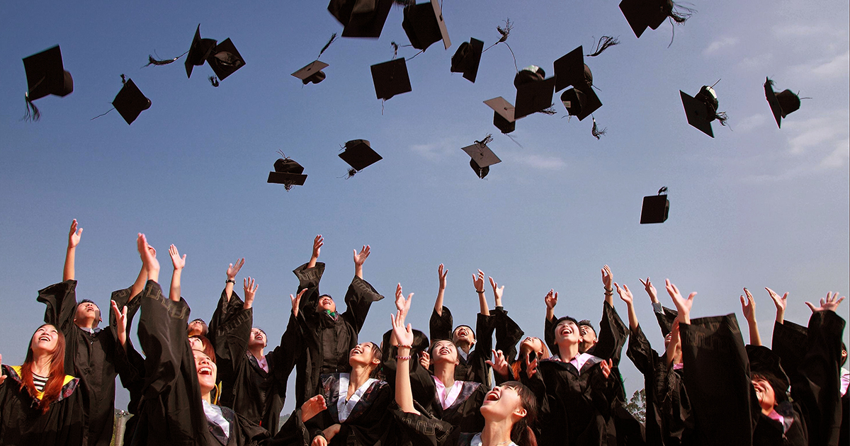 a group university graduates throw their mortar boards into the air