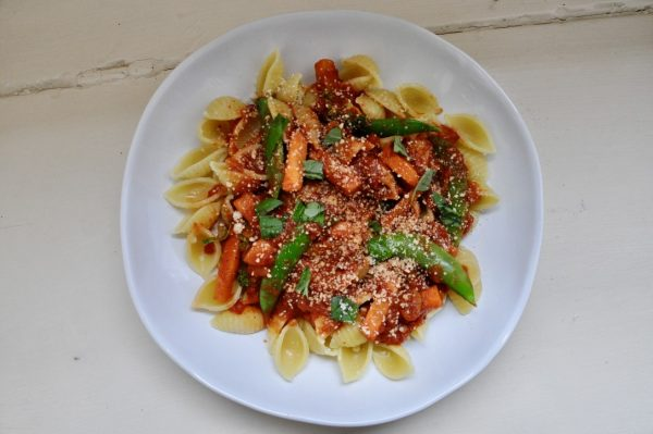 A bowl of pasta topped with sauce and vegetables