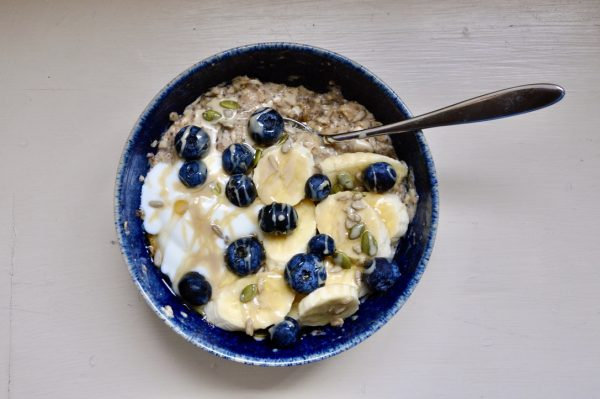 A bowl of porridge topped with bananas, blueberries, seeds, and yoghurt