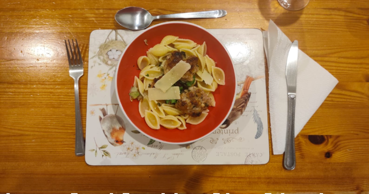 a plate of meatballs and spaghetti on a wooden table